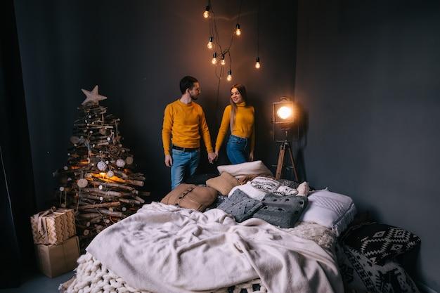 Kochająca para z poduszkami na łóżkowych girlandach na ścianie z ciepłym żółtym światłem