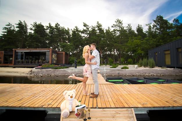 Kochająca potomstwo para całuje na drewnianym molu. lovestory na molo