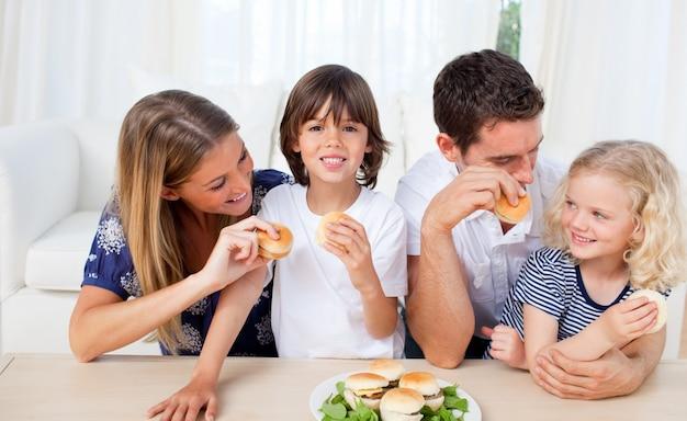 Kochająca rodzina jedzenie hamburgerów w salonie