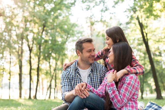 Kochająca rodzina siedzi w parku patrząc na siebie