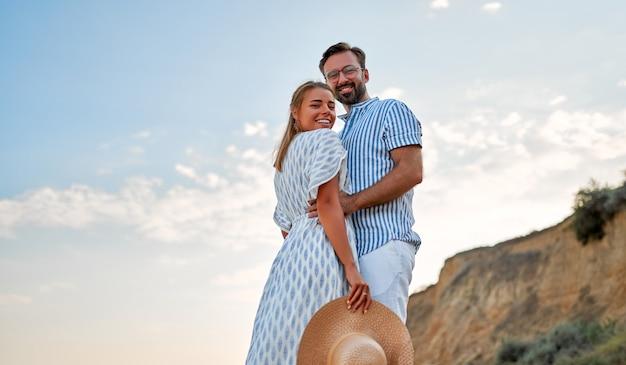 Kochająca się młoda para przytula się nad brzegiem morza, ciesząc się sobą i swoimi wakacjami. kobieta w sukience i mężczyzna w koszuli i białych spodniach przytulają się na plaży.