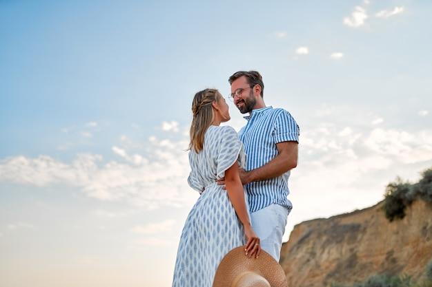 Kochająca się młoda para przytula się nad brzegiem morza, ciesząc się sobą i swoimi wakacjami. kobieta w sukience i mężczyzna w koszuli i białych spodniach spacerują po plaży.