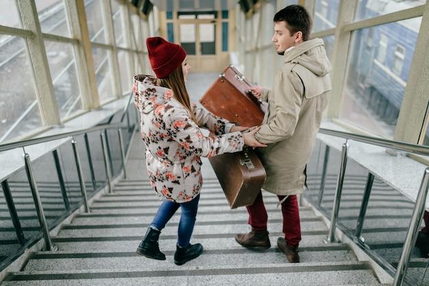 Kochająca styl życia para niosąca walizki po schodach.