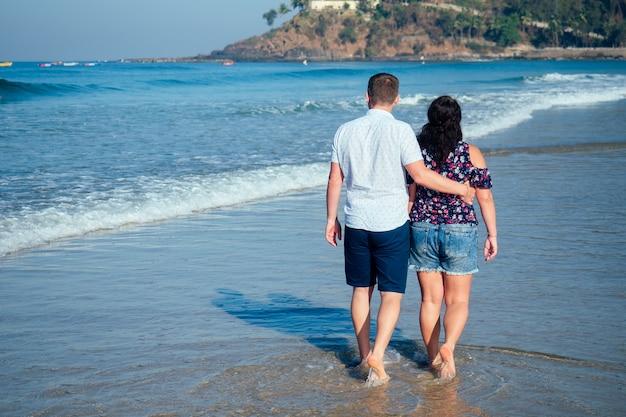 Kochająca szczęśliwa para spacerująca po plaży. romantyczne wakacje szczęśliwy miesiąc miodowy.