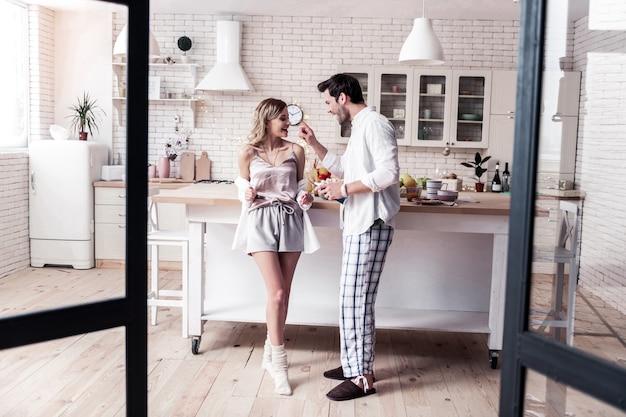 Kochająca zabawa. brodaty ciemnowłosy młody mężczyzna w białej koszuli i jego piękna żona śmiejąca się radośnie