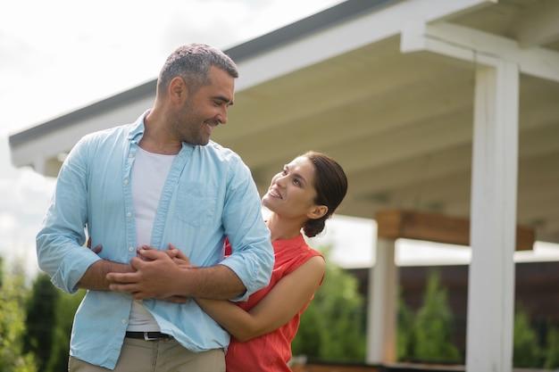 Kochająca żona. kochająca piękna żona uśmiecha się, przytulając swojego silnego przystojnego mężczyznę
