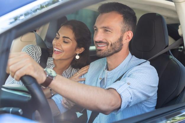 Kochająca żona przytulająca się. kochająca uśmiechnięta żona przytulająca swojego przystojnego brodatego męża prowadzącego samochód