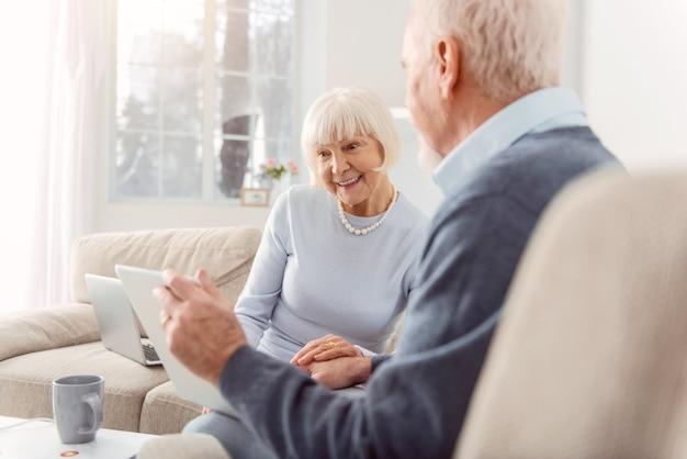 Kochający dziadkowie. miły starszy mężczyzna pokazujący żonie tablet ze zdjęciami ich wnuka, podczas gdy kobieta przygląda mu się z zabawnym spojrzeniem