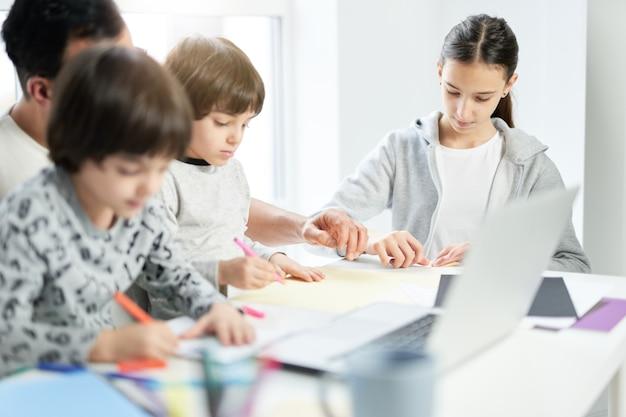 Kochający latynoski ojciec bawi się ze swoimi dziećmi. biznesmen za pomocą laptopa podczas pracy w domu i oglądania dzieci. freelance, blokada, koncepcja rodziny