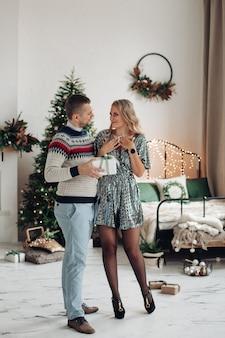 Kochający mąż daje swojej żonie świąteczny prezent. piękna kobieta zaskoczona prezentem od męża.