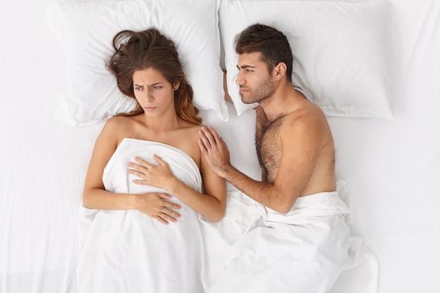 Kochający mąż stara się wspierać i uspokajać żonę, która ma jakieś problemy, leżeć razem w łóżku pod białą pościelą, wyrażać negatywne emocje. kłopoty rodzinne, związek i stresująca sytuacja