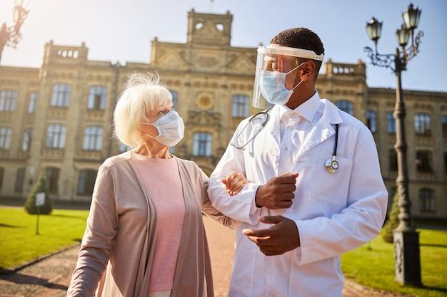 Kochający medyk asystujący starzejącej się pacjentce podczas spaceru po podwórku