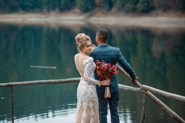 Kochający mężczyzna i kobieta w dniu ślubu nad pięknym jeziorem