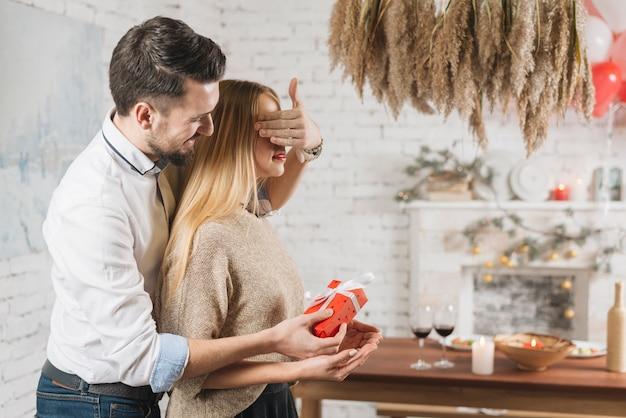 Kochający mężczyzna robi niespodziance dla kobiety
