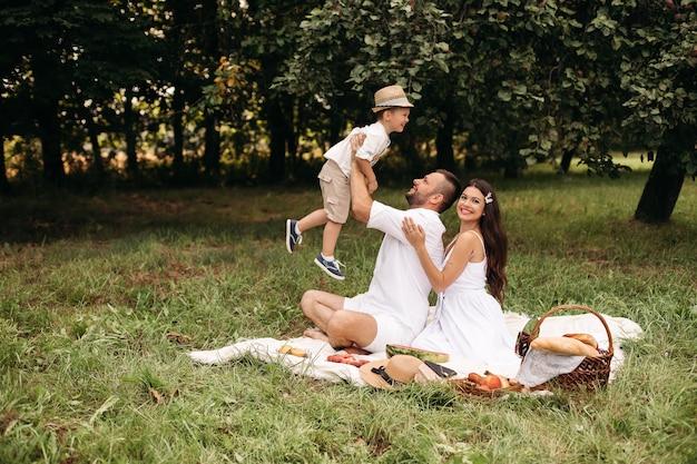 Kochający ojciec bawi się z synem, podczas gdy piękna matka obejmuje męża od tyłu. szczęśliwa rodzina kaukaski korzystających letni dzień w parku lub lesie na pikniku na trawie.