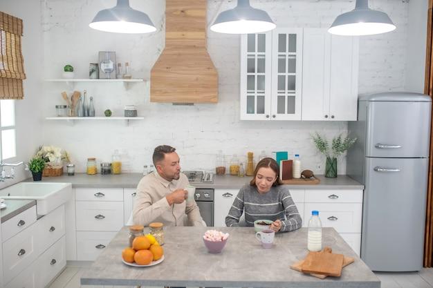 Kochający ojciec i wesoła córka rozmawiają przy stole podczas śniadania w domu w kuchni.
