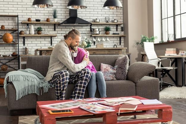 Kochający ojciec. kochający ojciec przytula swoją uroczą córkę, siedząc razem w salonie