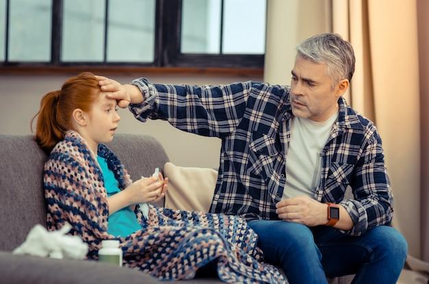Kochający ojciec. miły, przystojny mężczyzna sprawdzający temperaturę swojej córki, jednocześnie martwiąc się o nią