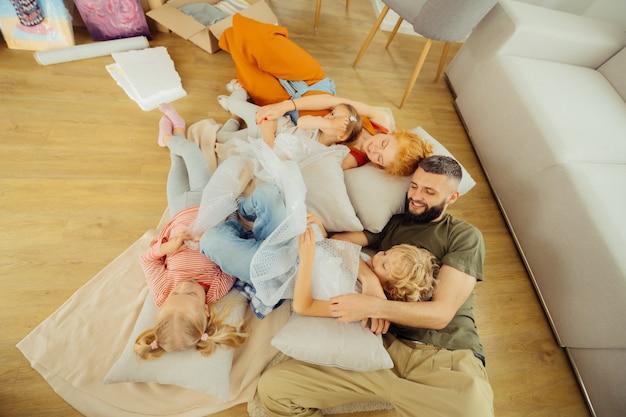 Kochający ojciec. szczęśliwy miły człowiek przytulający swojego śpiącego syna leżąc na łóżku