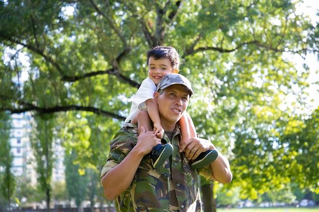 Kochający ojciec trzyma syna na szyi i spaceru w parku miejskim. szczęśliwy syn kaukaski siedzi na szyi taty w mundurze, przytulając go i odwracając wzrok. zjazd rodzinny, ojcostwo i koncepcja powrotu do domu