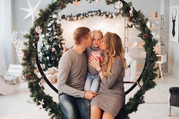 Kochający rodzice całują córkę na boże narodzenie.