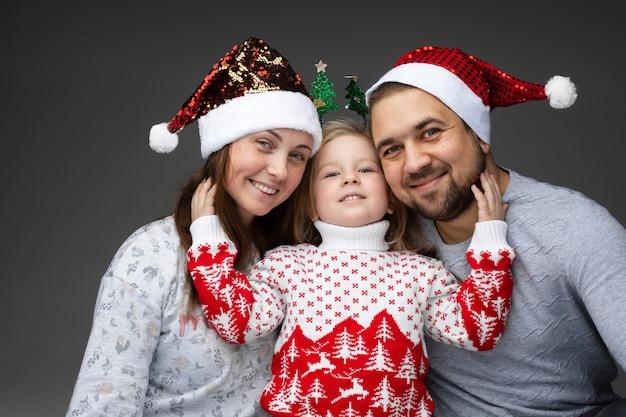 Kochający rodzice w czapkach mikołaja i ładna mała córeczka w zimowym swetrze, nosząca nakrycia głowy i obejmująca ich ramionami.