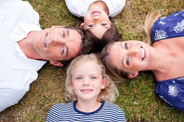 Kochający rodzinny lying on the beach w okręgu na trawie