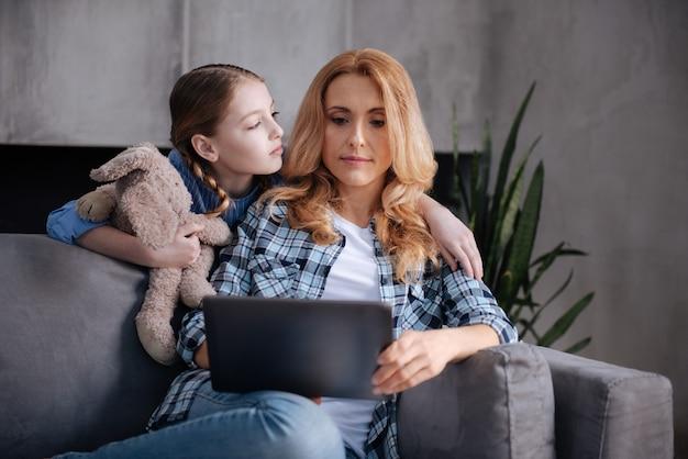 Kochający samotny rozczarowany dzieciak czekający na miłość matki w domu i przytulający rodzica, podczas gdy matka surfuje po internecie i używa gadżetu