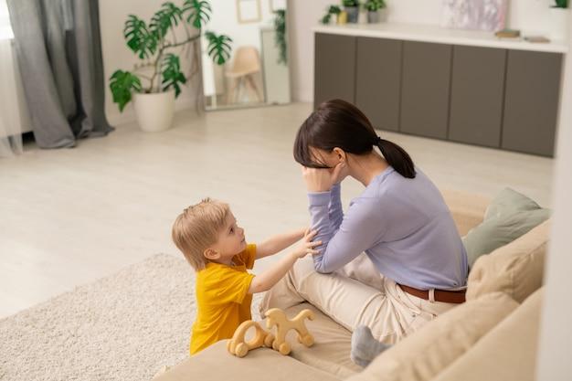 Kochający słodki synek dotykający ramienia matki, pocieszając ją, płacząc w salonie