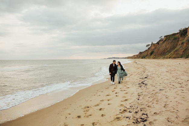 Kochający ślub para spaceru na plaży. piękna para ślubna na sesji ślubnej nad morzem