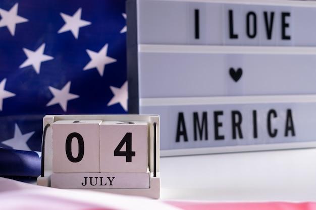 Kocham amerykę napisaną w lekkim pudełku na tle flagi usa. szczęśliwy dzień niepodległości usa.