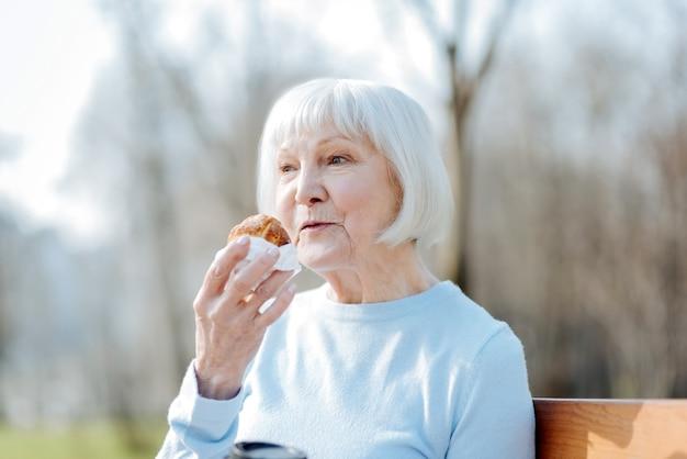 Kocham ciasteczka. zainspirowana stara kobieta cieszy się swoim ciasteczkiem i uśmiecha się