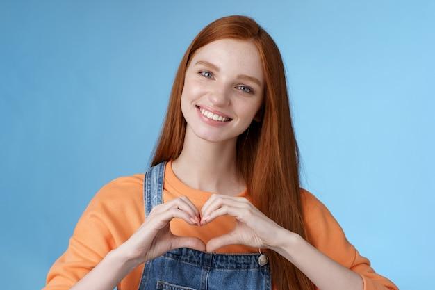 Kocham cię atrakcyjna romantyczna czuła ruda uśmiechnięta delikatna dziewczyna niebieskie oczy piegi pokazują serce klatka piersiowa wyrazić współczucie romantyczne pozytywne nastawienie wyznać namiętne głębokie uczucia uśmiechnięty słodki