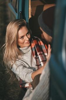 Kocham cię bardzo! widok z góry na piękną młodą kobietę patrzącą na swojego chłopaka i uśmiechającą się siedząc w niebieskim mini vanie w stylu retro