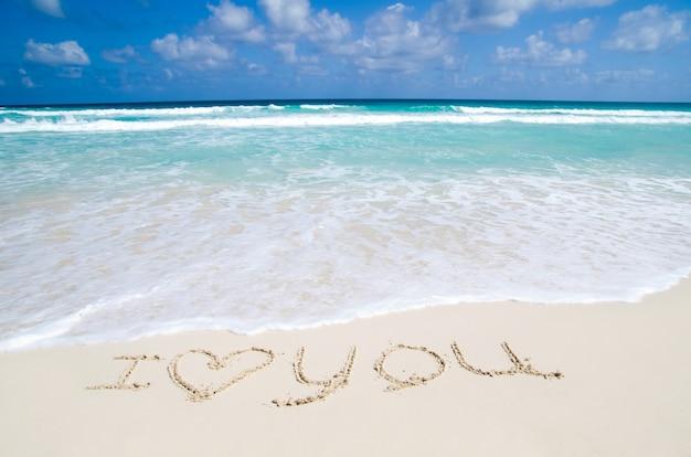 Kocham cię. cytat napisany na brzegu morza na tropikalnej plaży