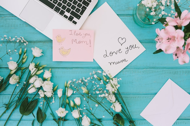 Kocham cię, mamo, napis z kwiatami i laptopem