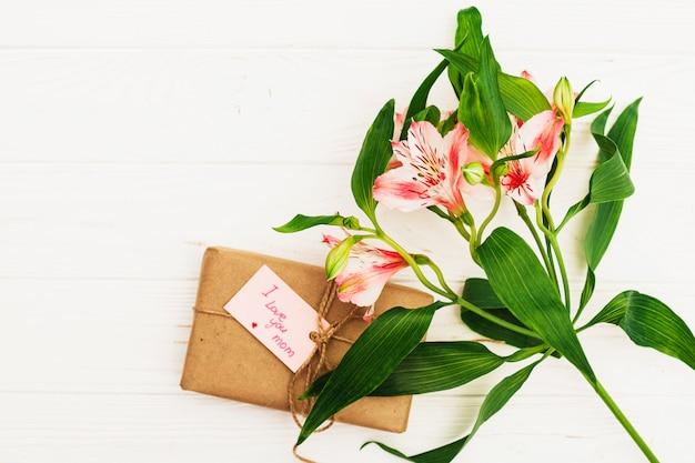 Kocham cię, mamo, napis z prezentem i różowe kwiaty