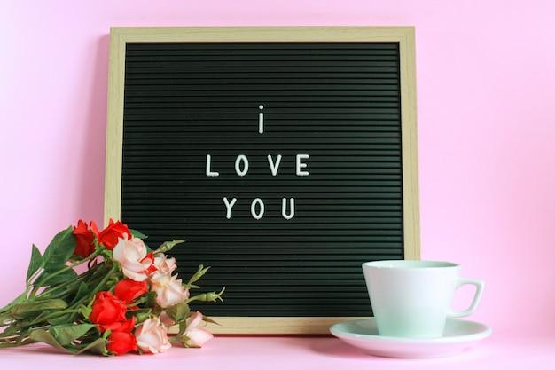 Kocham cię na tablicy z filiżanką kawy i róż na białym tle na różowym tle