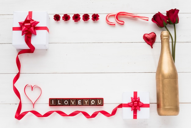 Kocham cię napis na kawałkach czekolady w pobliżu prezentów, kwiatów i butelki