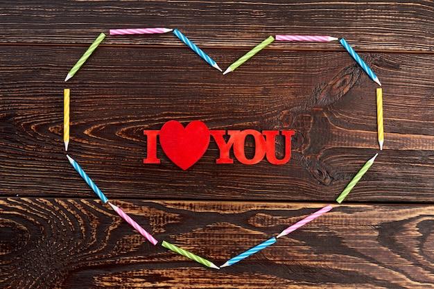 Kocham cię napis na podłoże drewniane. kształt serca z kolorowych świec. walentynki tło napis kocham na brązowym tle drewnianych. koncepcja wyznania miłości.