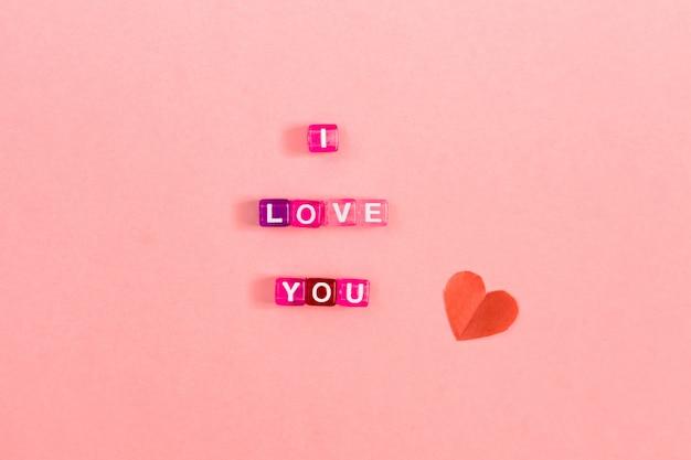 Kocham cię napis wykonany z kolorowych kostek z literkami. świąteczny różowy tła pojęcie z kopii przestrzenią