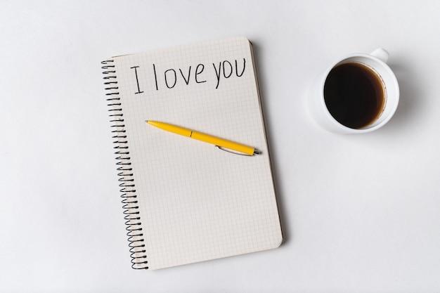 Kocham cię, napisane na zeszycie. poranna kawa i wiadomość dla ukochanych.