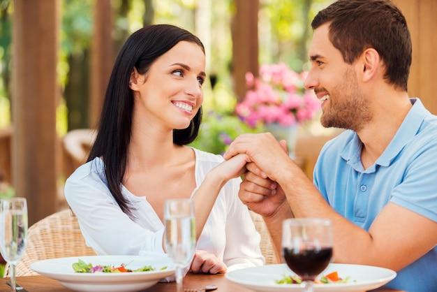 Kocham cię! piękna młoda kochająca para trzymając się za ręce i patrząc na siebie podczas wspólnego relaksu w restauracji na świeżym powietrzu
