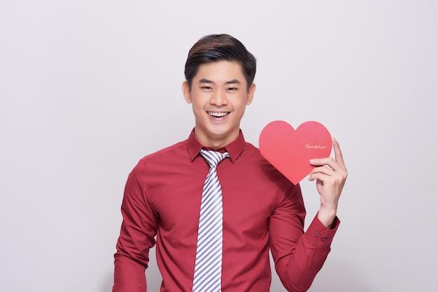 Kocham cię! przystojny młody mężczyzna trzyma kartkę walentynkową w kształcie serca i uśmiecha się stojąc na białym tle