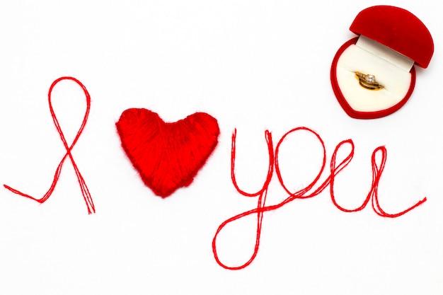Kocham cię słowa i symbol serca wykonany z czerwonej nici na białym tle na walentynki