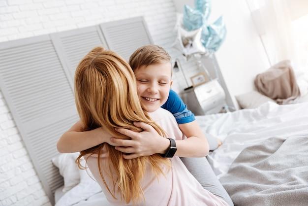 Kocham cię. szczęśliwy ładny zachwycony chłopiec, zamykając oczy i uśmiechając się, przytulając matkę