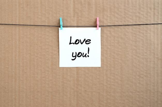 Kocham cię! uwaga jest zapisana na białej naklejce, która wisi na spinaczu na linie na tle brązowej tektury