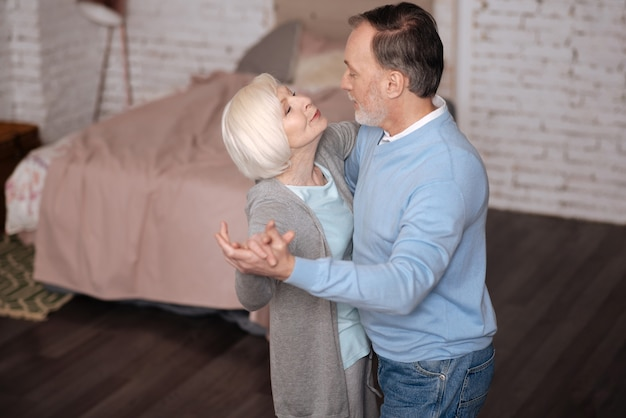 Kocham cię. widok z góry wieku mężczyzny i kobiety stojących i tańczących razem, patrząc na siebie w domu.
