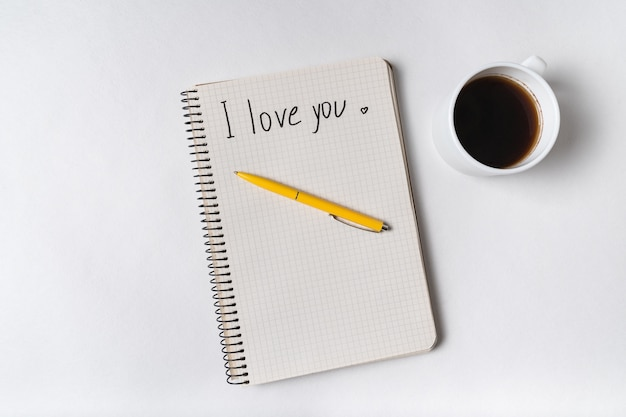 Kocham ciebie napisane na zeszycie na białym. poranna kawa i wiadomość dla ukochanych