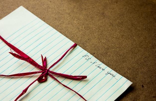 Kocham ciebie ręcznie pisząc napis na notatce w miejscu pracy lub na stole. pocztówka walentynki koncepcja miłości na dzień matki z miejscem na tekst
